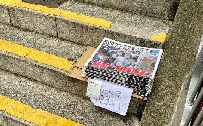 ▲黎智英被捕隔日,香港市民透過購買報紙「稱蘋果」,街上可見到有民眾將多購買的報紙分享給路人。(圖/翻攝自