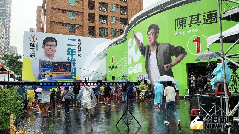 ▲陳其邁的支持者從下午3點起陸續湧入競總,下午4點投票結束,陳其邁的支持者穿雨衣、撐雨傘,不畏風雨看著舞台前方的電視開票。(圖/記者郭俊暉攝)