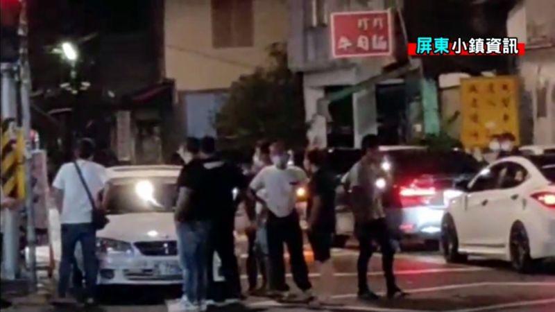 ▲店家與客人糾紛在警局處理雙方撂人支援,一群年輕男子,手插著腰,聚集在街上。(圖/屏東小鎮資訊提供