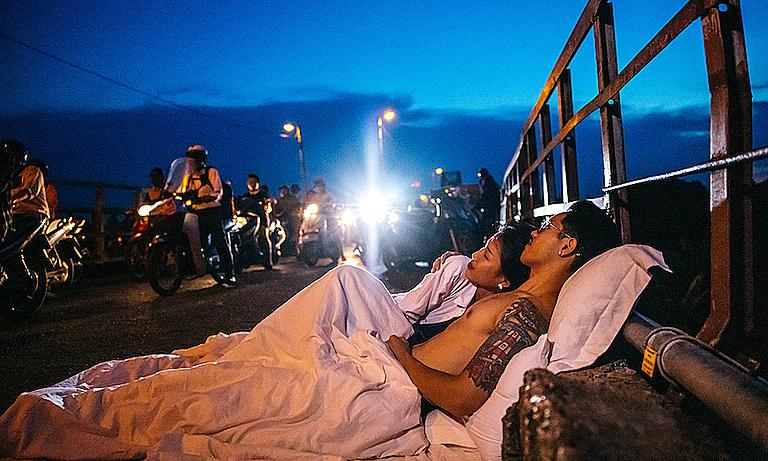 ▲一對來自越南的情侶屏棄唯美的裝飾佈景,選擇把枕頭和棉被搬到街上,拍攝出一系列在街上共眠的奇特婚紗照。(圖/翻攝自臉書)