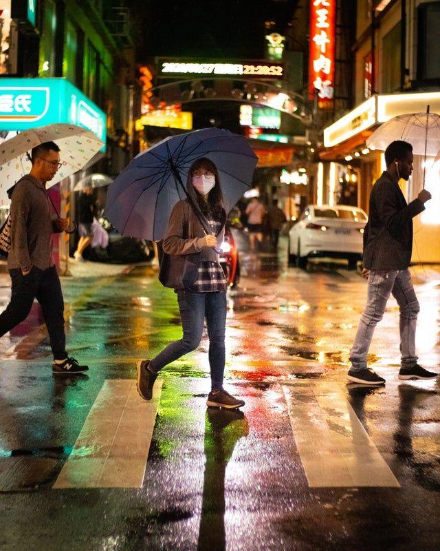 ▲路人手持雨傘穿越斑馬線