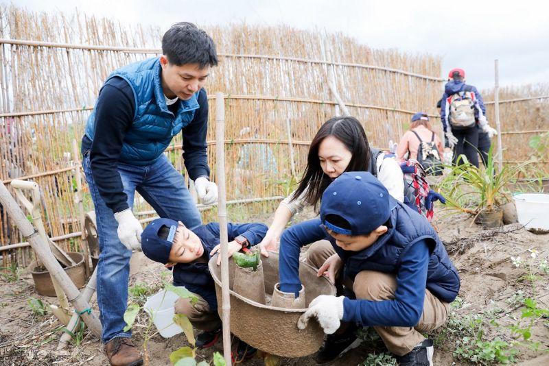 ▲現場也有9歲的雙胞胎兄弟參與,協力將植株露出的部分穿過水寶盆。(圖/中信銀行提供)