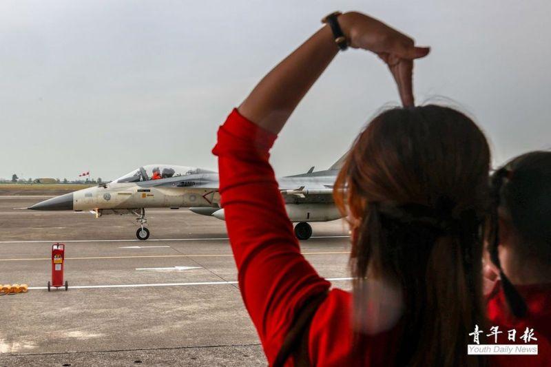 ▲空軍1聯隊歡迎參加天龍操演官兵凱璇榮歸,飛行員太太抱著女兒向偉大的英雄丈夫比出大大的愛心手勢,感謝他為國、為家全力以赴。(圖/青年日報提供)