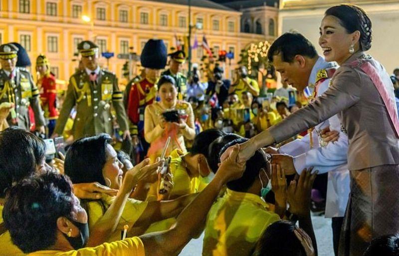 ▲瓦吉拉隆功與王后蘇堤達在皇宮外接見身著黃衣的支持者。(圖/翻攝自每日郵報)