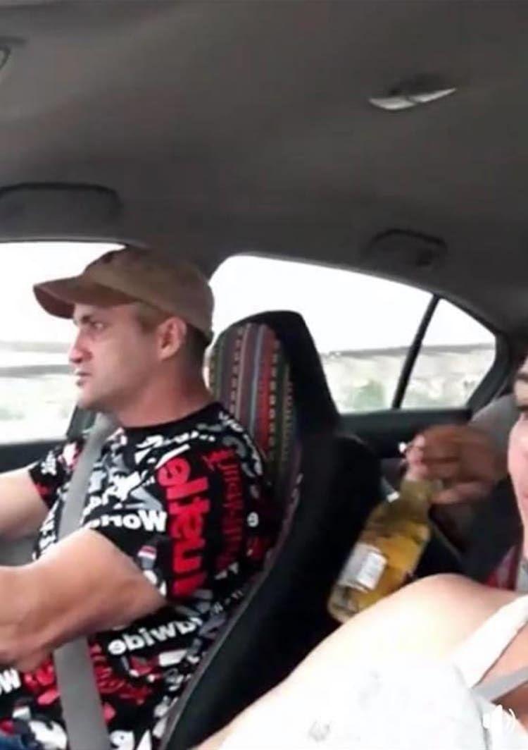 ▲後座友人將酒瓶遞給駕駛。(圖/翻攝當事人臉書)