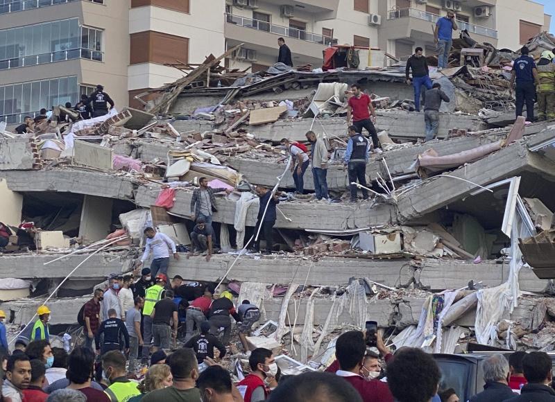 ▲愛琴海區域在當地時間周五晚間發生芮氏規模 7 級大地震,圖為災情慘重的土耳其城市伊茲米爾,救難人員在倒塌的建築物上搜救的畫面。(圖/美聯社/達志影像)