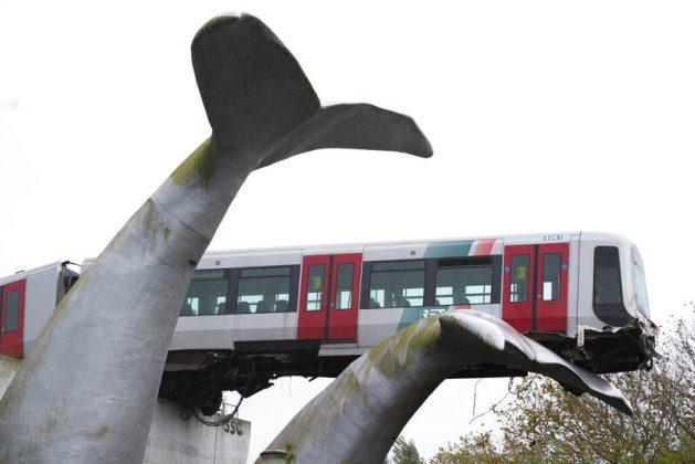 ▲衝出軌道的火車幸運地被一座鯨魚尾巴公共藝術撐起。圖/取自美聯社