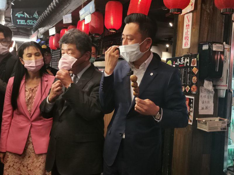 ▲陳時中拉開口罩品嘗使用台灣國產豬肉製成的新竹貢丸串燒。(圖/記者金祐妤攝,109.11.18)