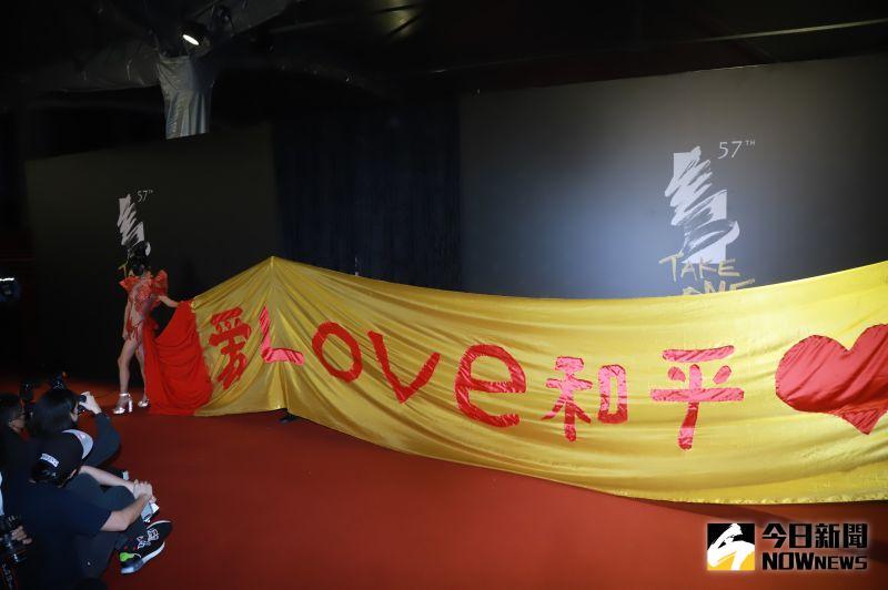 ▲白靈身後用黃色布料寫下「愛LOVE和平」。(圖/NOWnews影像中心)