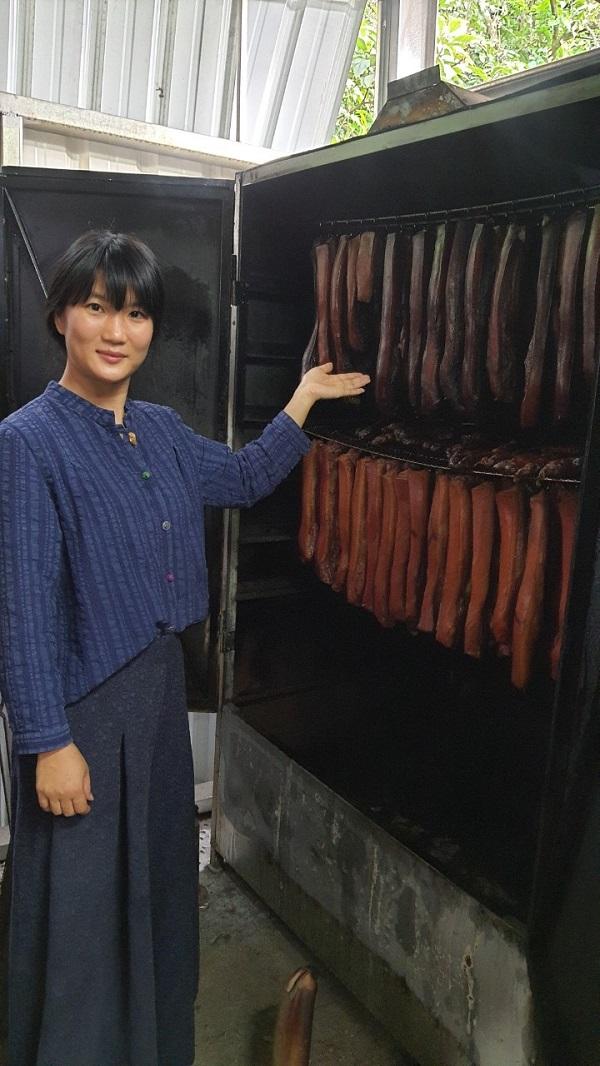 ▲新住民歐陽玲麗與她的煙燻臘肉。(圖/移民署提供)