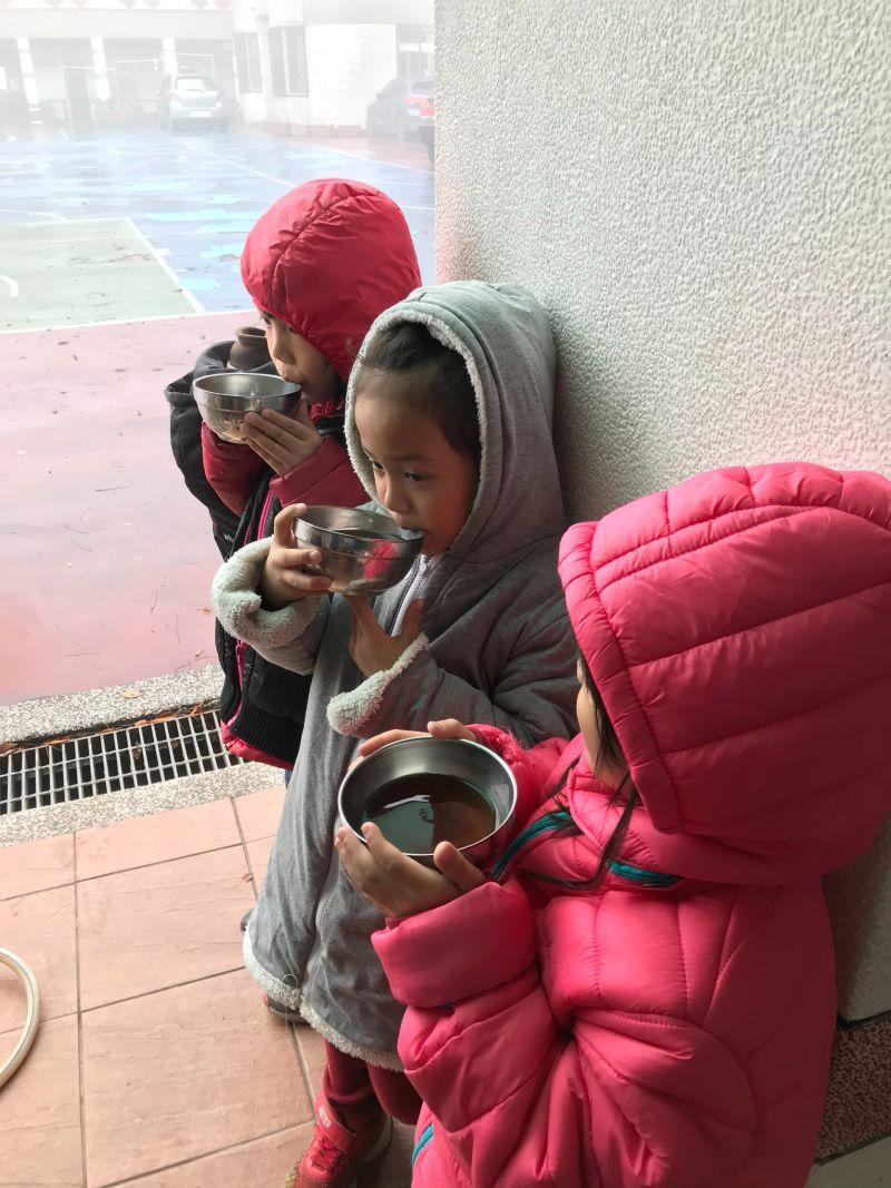 ▲巴崚國小學童正在引用校方提供的熱飲禦寒。(圖/桃園市教育局提供)