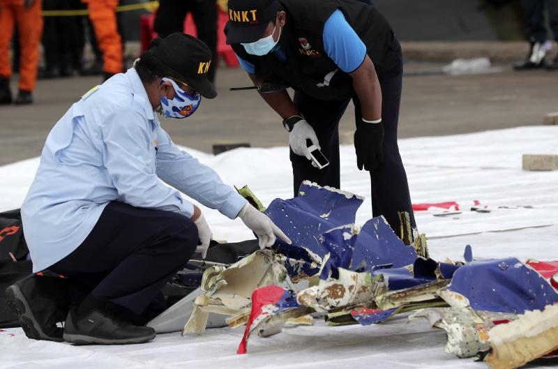 ▲印尼國家搜救局檢視打撈到的、疑似機身殘骸的物件,此外還有其他被認為是乘客物品的打撈物。(圖/美聯社/達志影像)