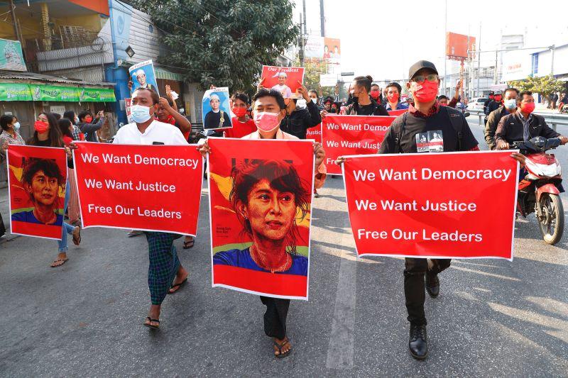 ▲緬甸民眾手拿翁山蘇姬、溫敏的頭像在街上抗議。(圖/美聯社/達志影像)