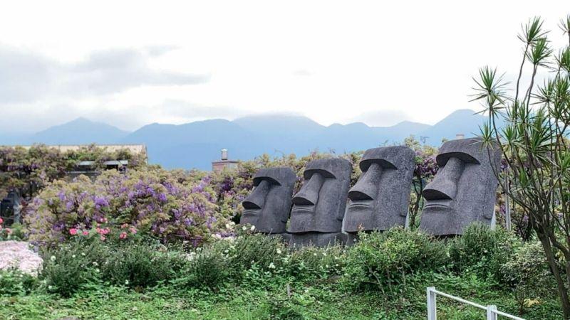 ▲一旁還有整排巨型摩艾石像,用反差萌的石像配上粉紫花海營造最美打卡點。(圖/紫藤咖啡園(一店)(屯山園區)臉書)