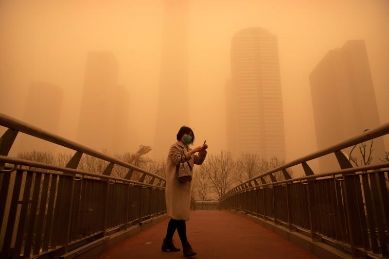 ▲中國北方遭逢近10年最強沙塵暴,北京市15日一早便是昏黃一片。(圖/美聯社/達志影像)