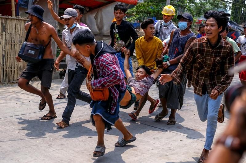 ▲隨著緬甸人與軍政府的對抗越發猛烈,更多流血衝突也隨之發生,且因示威者質疑北京暗中支持軍政府,連在當地經商的外資企業都被波及。圖為14日在仰光,示威群眾帶著一名遭軍警打傷的民眾逃離現場。(圖/美聯社/達志影像)
