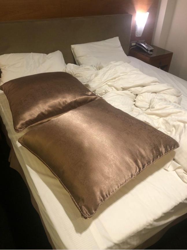 ▲原PO一入住飯店,就發現床上放了兩顆褐色大枕頭。(圖/翻攝Dcard)