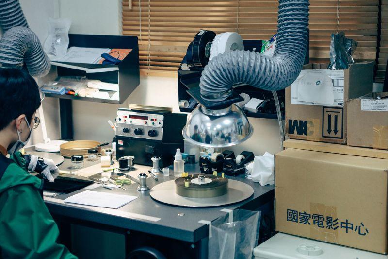 ▲樹林片庫中的電影膠卷整飭區,工作人員正專注於檢視膠卷的每一格狀況。