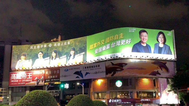 高雄市五福、中華路口日前出現一塊巨型看板,右邊是以民進黨宣傳政績為主,左邊則是出現四位市議員參選人的形象照,引發黨內質疑。(圖/讀者提供)
