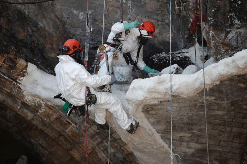 ▲在無法搭建鷹架的地方,工人透過垂吊的方式進行修復工作。(圖/美聯社/達志影像)