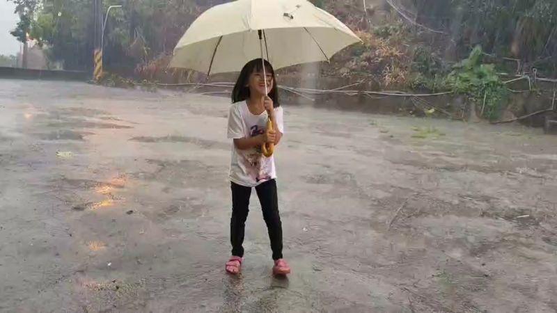 ▲高雄市桃源區下起大雨,部落的小朋友們撐著雨傘到雨中玩水,超開心。(圖/翻攝畫面)