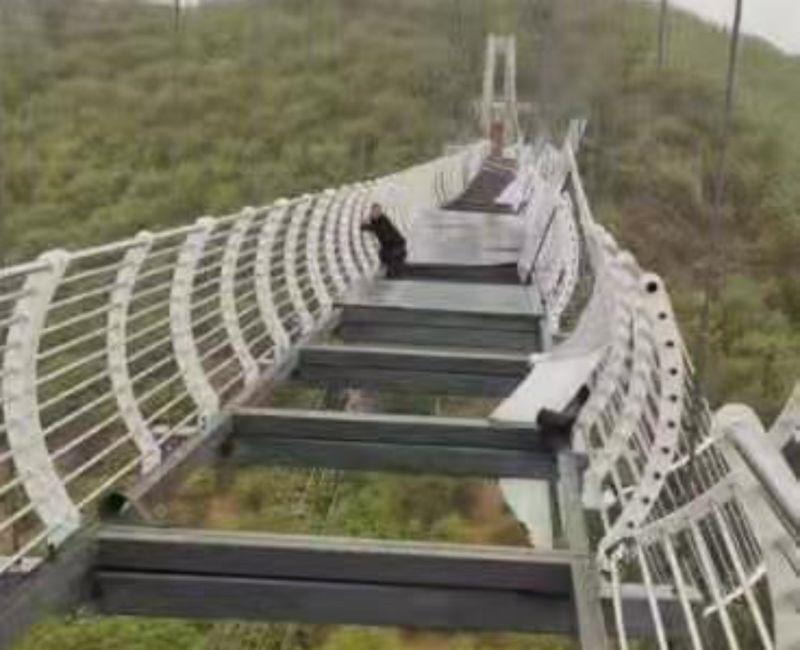 ▲中國吉林琵岩山風景區,7日傳出有男子一度被困在遭強風掀翻玻璃踏板的棧道上,險象環生,所幸最後順利脫困。(圖/翻攝自微博)