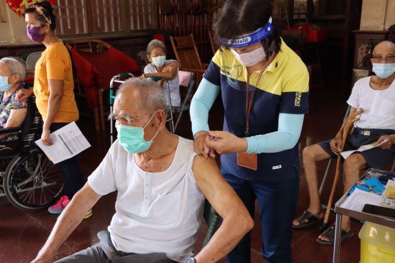 ▲田寮進天宮接種站,長輩坐在位置上施打疫苗。(圖/高雄市政府提供)