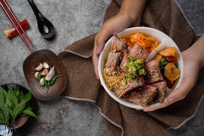 ▲台中知名燒肉店昭日堂七月新推升級版便當,標榜高檔牛排平價供應,滿滿溢出來的肉品,讓人看得垂涎。(圖/業者提供)