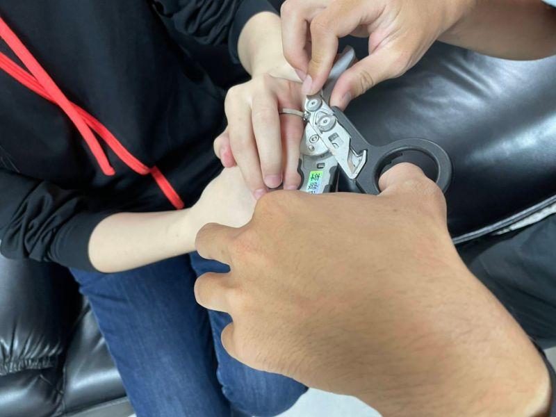 ▲消防隊員徵得少女同意後,小心地用戰術剪刀一剪,順利解決了少女的「卡指」危機。(圖/桃園市消防局提供)