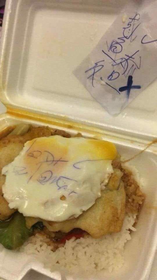 ▲老闆把寫過字的紙條放在餐盒裡面忘記拿出來,一顆荷包蛋被印上了原子筆的墨水。(圖/翻攝爆廢公社)