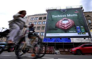 ▲德國街頭有著梅克爾招牌菱形手勢的商業廣告,上面用德語寫著「再見了媽媽」。(圖/美聯社/達志影像)