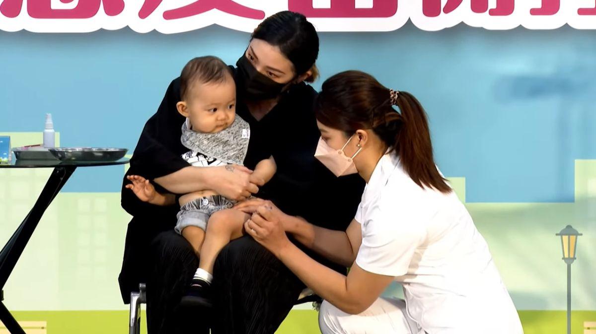 ▲防疫大使譚艾珍的孫子「新醬」於記者會現場,率先施打流感疫苗。(圖/翻攝自疾管署直播訊號)